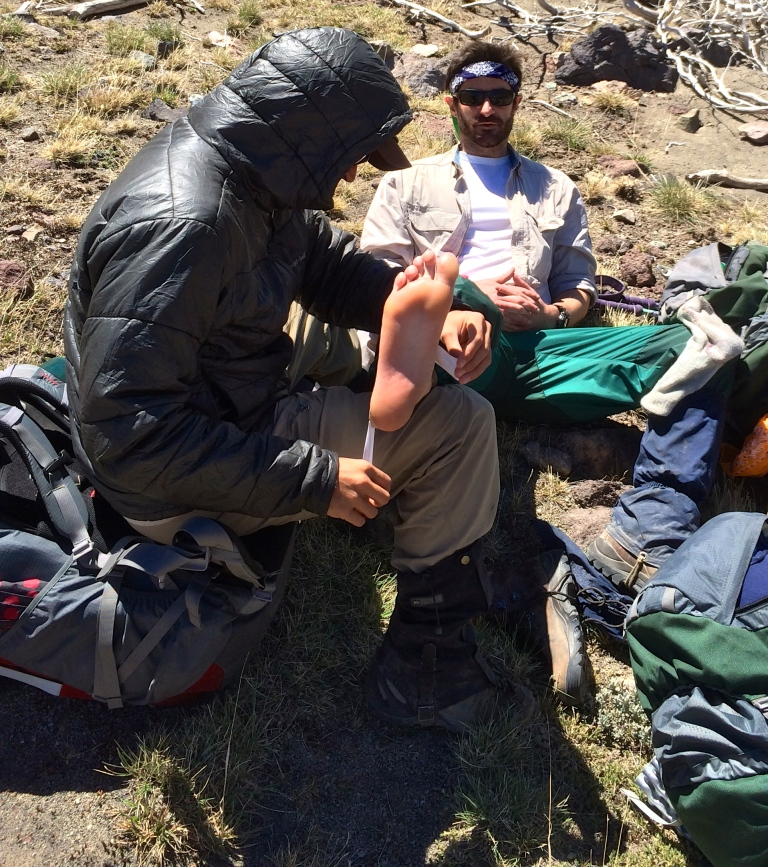Miles Yourman takes a break from hiking to repair his feet.